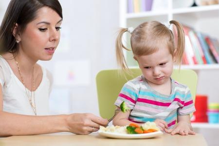 petite fille triste: fille de l'enfant regarde avec dégoût des légumes sains. Maman convainc fille à manger de la nourriture.