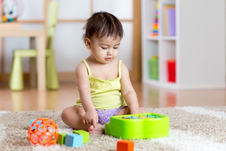 Child toddler with develepmental toys. Early education for kids. Colorful wooden art toys. Little girl play music. Kid with piano.