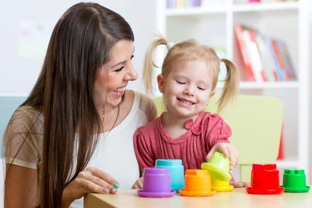 niños ayudando: lindo madre y sus juguetes juego de los niños en el interior