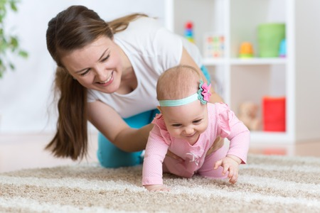 Funny crawling baby girl with mother in nursery Stock Photo