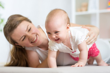 nursery education: Happy crawling baby girl with mother in nursery