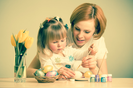 mother and child daughter with brush coloring easter eggs photo