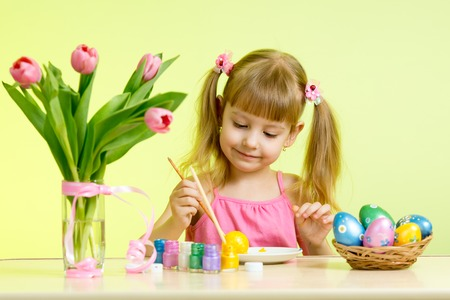 Kid girl with brush coloring easter eggs photo