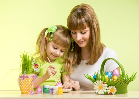 mother and kid girl painting easter eggs together photo