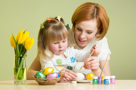 happy mother teaches child daughter to paint easter eggs photo