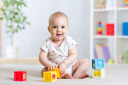 baby toddler playing color cubes toys at home room or nursery Foto de archivo