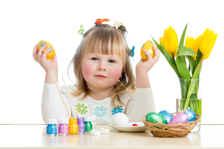 Kid girl with brush coloring easter eggs isolated photo