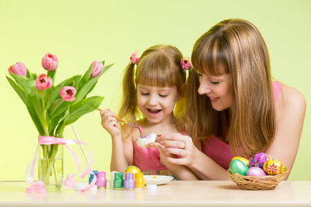 mother and child daughter preparing to Easter holiday and with brush coloring eggs photo