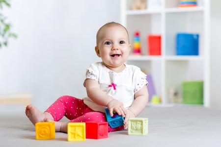Bebé que juega los cubos de los juguetes del bloque en el hogar