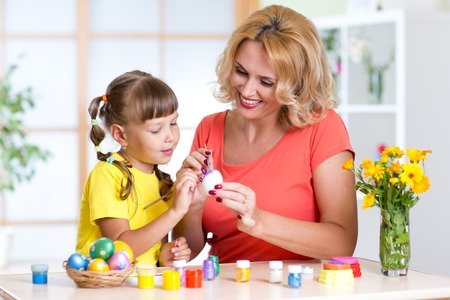 teaches: happy mother teaches child daughter to paint easter eggs