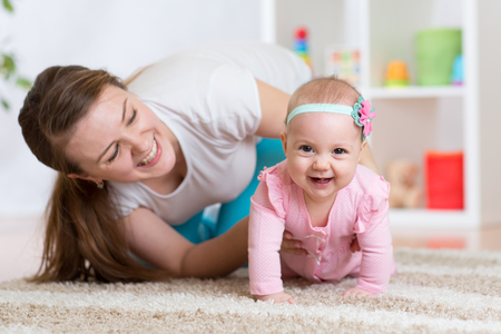 Funny crawling baby girl with mother in nursery Reklamní fotografie - 54307361