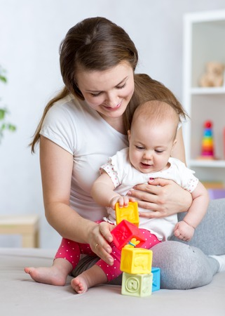 baby playing toy: Mother and baby girl playing with educational toys in living room
