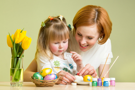 happy mother teaches child daughter to decorate Easter eggs photo