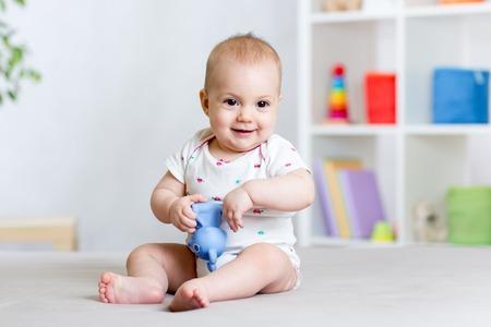 bebe sentado: alegre bebé jugando con juguetes en el hogar
