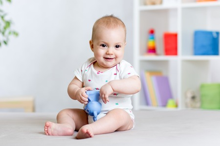 baby nursery: cheerful baby playing with toy at home Stock Photo