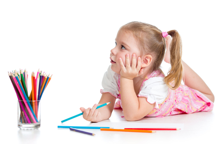 kid girl drawing with color pencils isolated on white photo