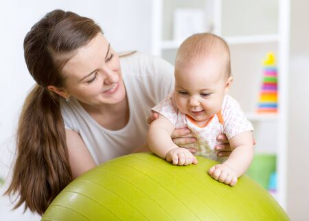 baby playing: mother playing with baby on fit ball