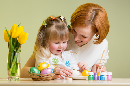 3 5 years: mother and kid girl painting easter eggs together Stock Photo