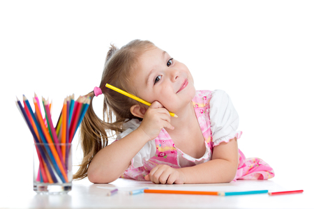 Cute cheerful child girl drawing using color pencils photo
