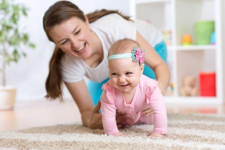 Grappig kruipende baby meisje met moeder thuis Stockfoto