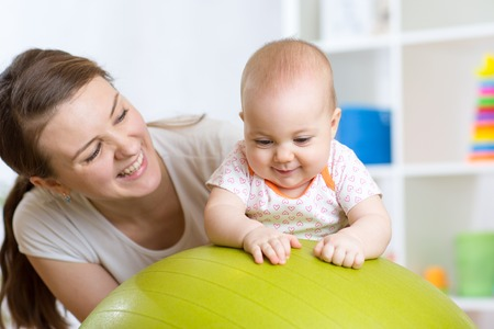Mother with happy child doing exercises with green gymnastic ball at home. Concept of caring for the baby's health. Standard-Bild