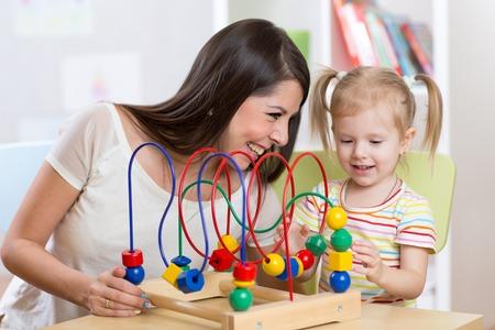 developmental: happy kid girl and mom playing developmental toy