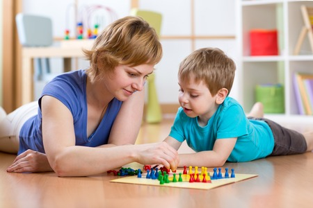mother board: Family mother and son kid playing board game ludo at home on the floor Stock Photo