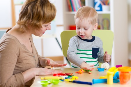 day care center: kid boy and woman play colorful clay toy in nursery or day care center