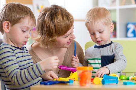 vrouw leert kinderen handwerk op de kleuterschool of peuterspeelzaal of kinderdagverblijf