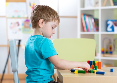 playschool: Education image from kindergarten or playschool. Child boy playing with toys at table