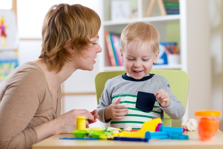 little dough: Little boy is learning to use colorful play dough with mother help in nursery Stock Photo
