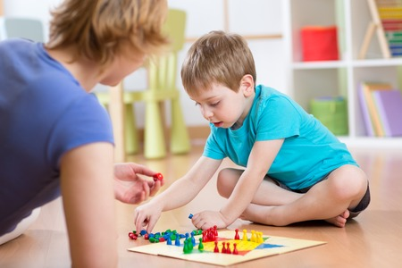 ludo: Mother and her son playing in board game on floor in nursery Stock Photo