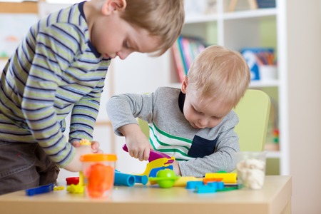 clay modeling: Kids Play Modeling Plasticine, Children Mold Colorful Clay Dough.  Preschooler Playing Together in Nursery