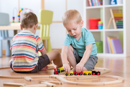 brothers: Children playing rail road toy in nursery