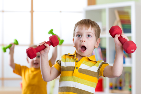 Funny kids boys exercising with dumbbells. Healthy life, sportive children. Stock Photo