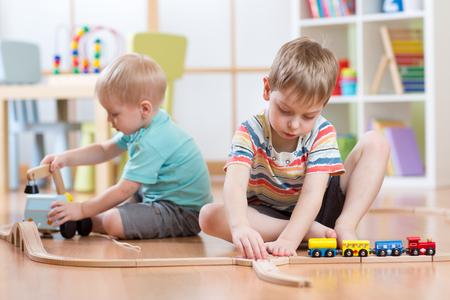 jugando: Muchachos de los niños que juegan con juguetes educativos y de ferrocarril edificio