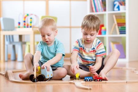 family and friends: Children playing rail road toy in nursery