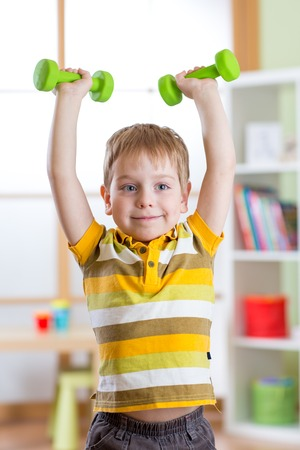 healthy sport: Smiling kid little boy exercising with dumbbells. Healthy life and sport concept.