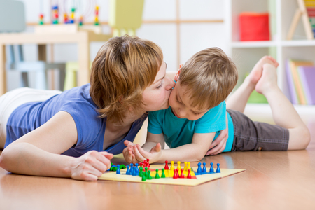 Family mother and son kid playing board game ludo and kissing at home on the floor