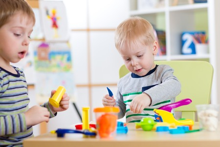 day care center: Happy children friends playing with plasticine at home or day care center