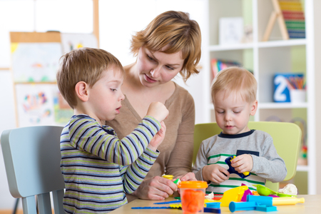 Woman and kids have a fun in daycare center