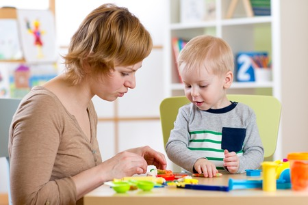 day care center: Child boy and woman play colorful clay toy in nursery or day care center