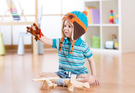 persona alegre: niño feliz niño juega con avión de juguete y el sueño de convertirse en un piloto Foto de archivo