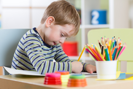 one room school house: Preschool child boy use pencils and paints for homework received from kindergarten Stock Photo
