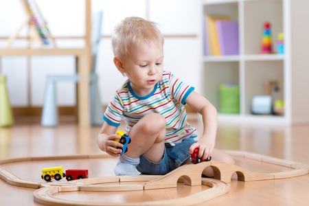 baby toys: Child boy playing rail road toy in nursery