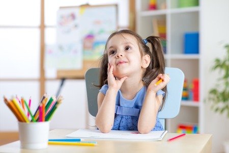 day care: dreamy child girl drawing with color pencils