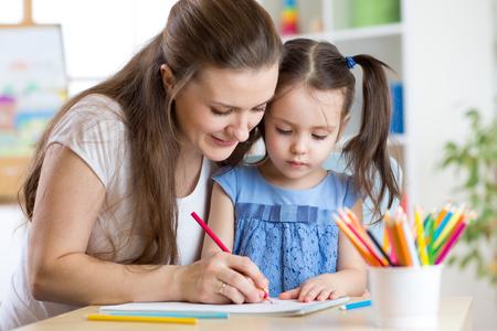 어머니와 그녀의 아이가 함께 연필을 그립니다. 스톡 콘텐츠