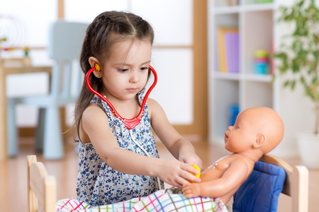 child girl playing doctor with doll at home Stock Photo - 53471284