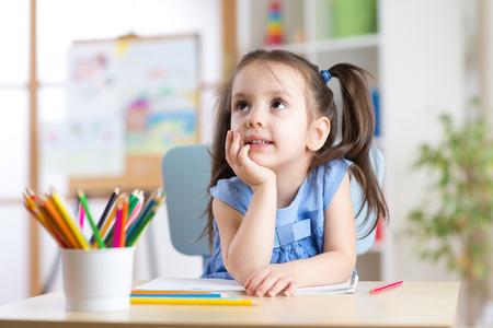 muchacha niño soñador dibujo con lápices de colores en la guardería