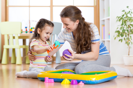 kinetic: Child girl and mother playing with kinetic sand at home Stock Photo